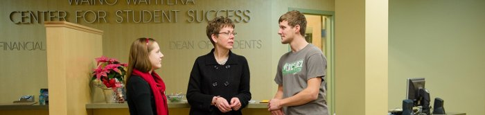 Dean of Students Bonnie Gorman talks with students at the front desk in the Wahtera Student Success Center