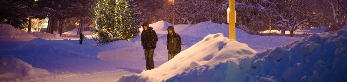 Two students walk through campus during a winter snowfall