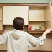 A women looking into an empty pantry.