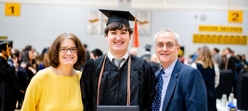 A new graduate and his parents at midyear commencement.
