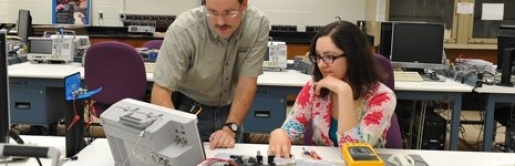 A professor showing a student a piece of lab equipment.