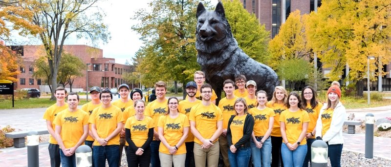 The LEAP group poses by the Husky statue on the campus of Michigan Tech.