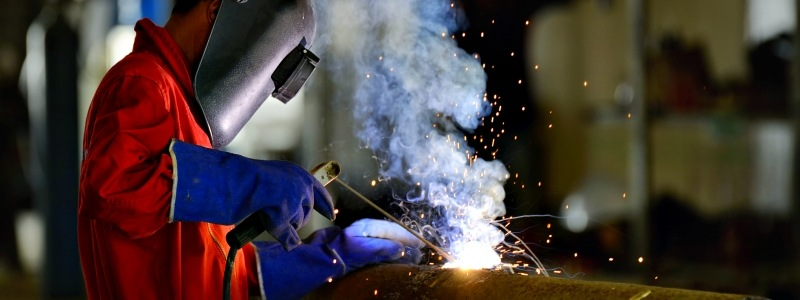 Welder using proper safety equipment to cut through metal.