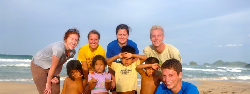 Michigan Tech students with Panamanian children on the beach.