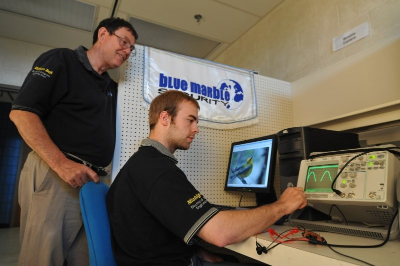 an advisor looks on as a student works with electronic equipment