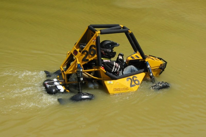 A baja racer driving through a pond