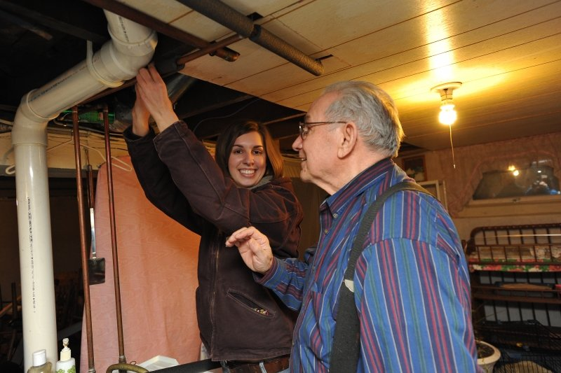 A young woman fixes a heating duct while an older homeowner watches