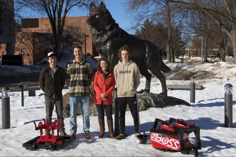 Four people and two robots in front of the Husky statue