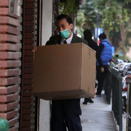 A man in a mask delivering a box