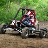 A mini baja car races on a dirt track