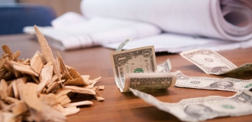 Photo of dollar bills, wood chips, and paper shown on a wooden table.