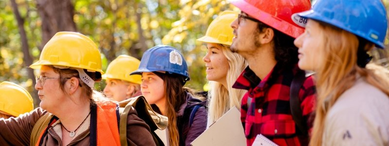 Students in a forest, wearing hard hats.