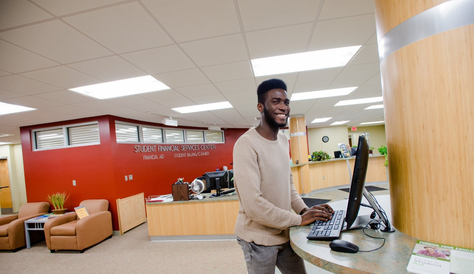Student at a computer in the Financial Aid office.