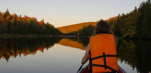 Girl paddling a canoe on still water with forest in the background.