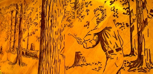 Wood mural of logger chopping down a tree.