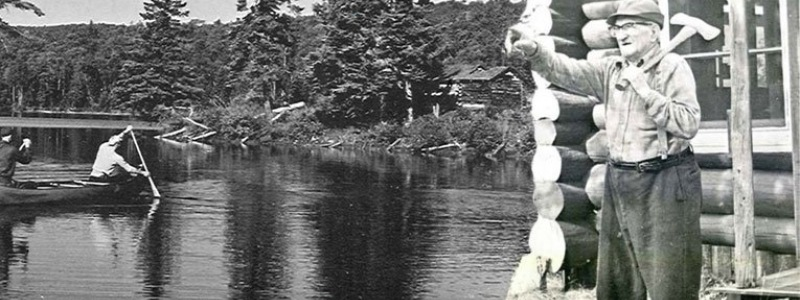 Black and white photo of people with an axe and canoeing.