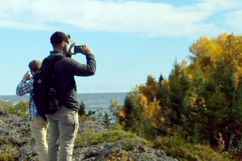 Two people taking photos of a vista of a forest and a lake.
