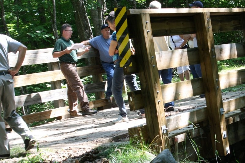 Researchers standing on a wooden bridge.