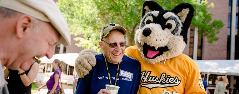 Alumnus standing with Blizzard T. Husky at reunion.
