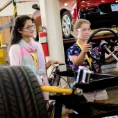 Two women work on a car in a lab.