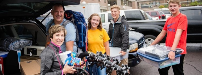 Parents and students unload a minivan on move-in day.