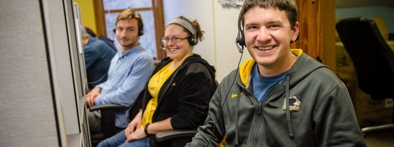 Three students wearing headsets make phone calls for the Tech fund.