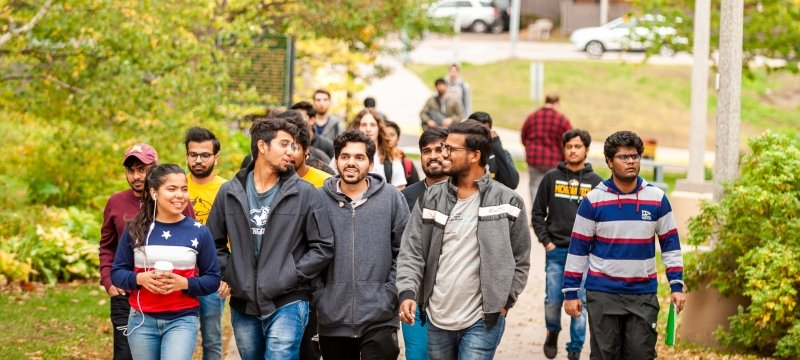 A group of students walks on the campus mall in early fall.