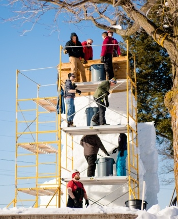 Students on scaffolding working on a snow statue.