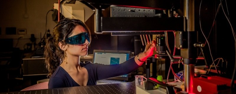 Graduate student working with lasers.