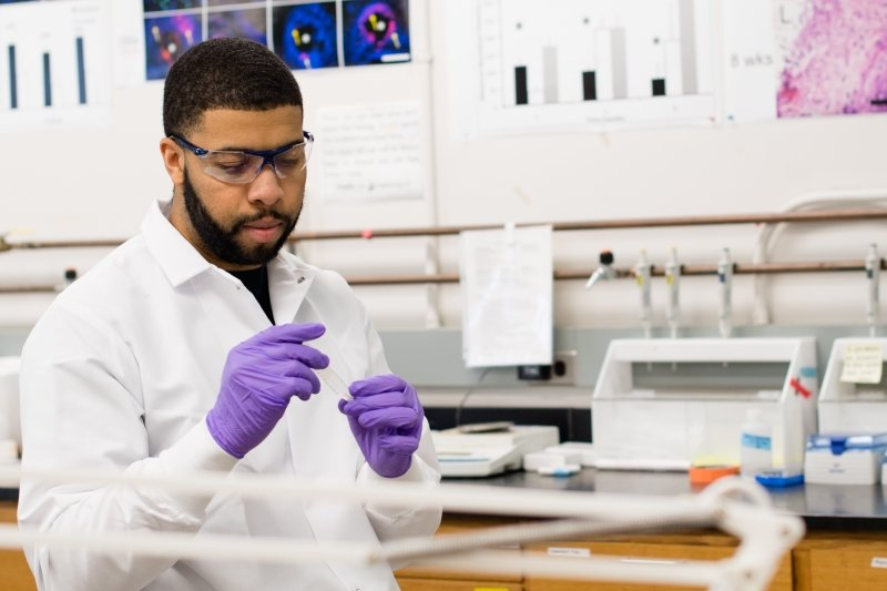 Graduate Student Researcher in a lab with lab gear on.