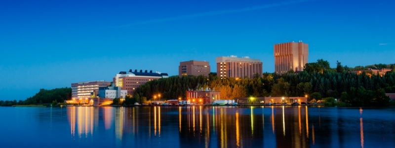 Michigan tech campus at dusk with dark blue sky and colored lights reflecting on water