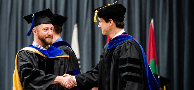 Graduate faculty shaking hands with graduating student