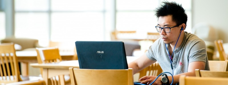 student in bright library studying at computer