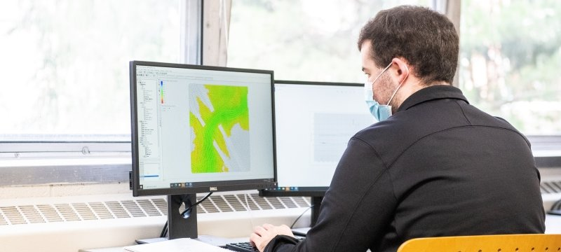 Researcher sitting at computer looking at a geographical map