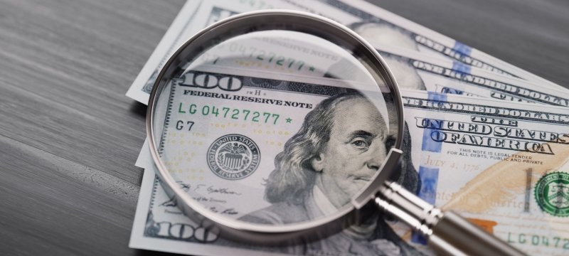 A magnifying glass on top of $100 bills.