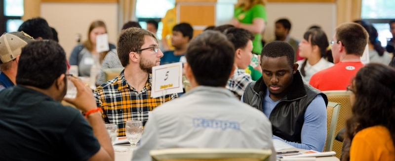 Graduate students meet around a table at orientation.