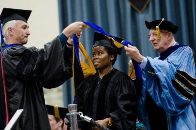 A grad student receiving honors draping over shoulders at commencement.