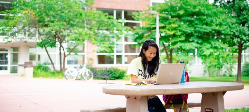 Student sitting outside at a table with a laptop.