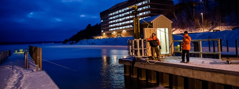 Two researchers using dock equipment during a cloudy winter evening on the dock of the GLRC