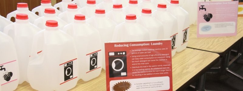 Gallon bottles of water lined up with instructional signs for Reducing Consumption: Laundry