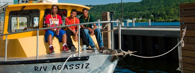 Three high school students sitting on the bow of the RV Agassiz tied to the dock of the GLRC