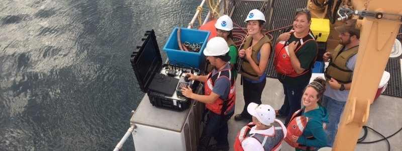 A group of researchers looking up at the camera on a research vessel.