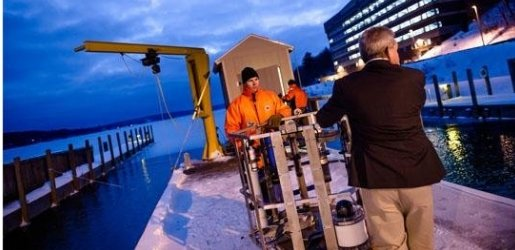 Two researchers move equipment on the dock of the GLRC on a winter's evening.