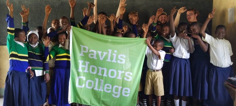 Students holding a Pavlis Honors College flag