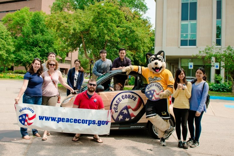 A group stands in front of a Peace Corps car