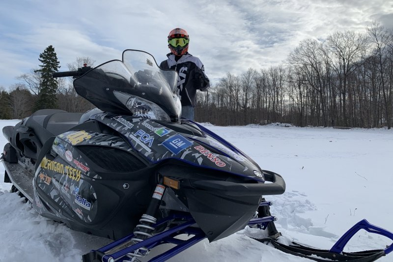 A person in full gear stands behind a snowmobile