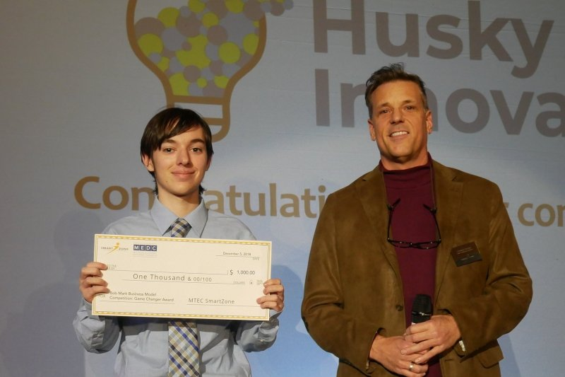 A student poses with his check after winning a venture competition