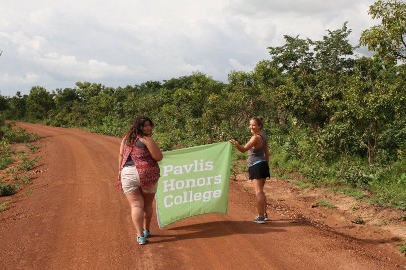 two women holding a Pavlis Honors College banner