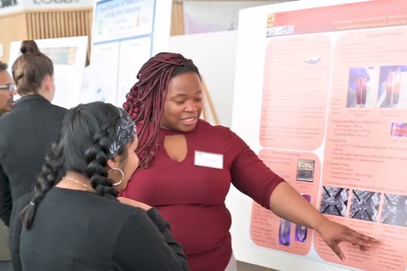 A student discusses her research poster at a forum