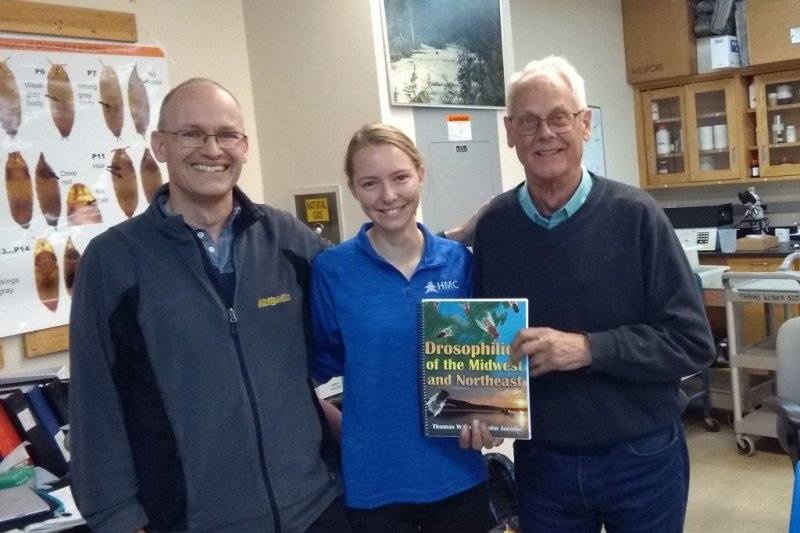 Two faculty members and a student researcher pose with the textbook they wrote